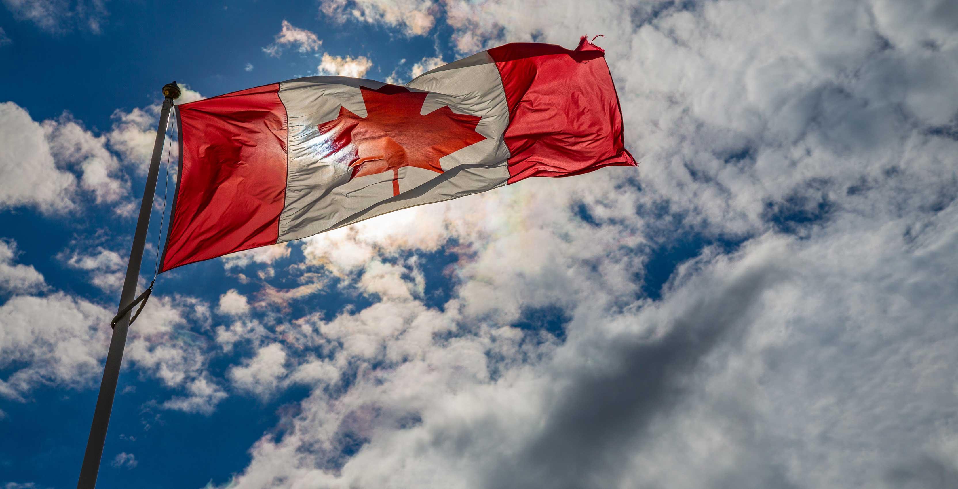 Une image du drapeau canadien flottant au vent sur un fond de nuages